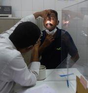 En läkare undersöker en man i Indien för mukormykos.  Rafiq Maqbool / TT NYHETSBYRÅN