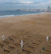 Aktivister i skyddsdräkter gräver symboliska gravar på Copacabana i Rio de Janeiro. Leo Correa / TT NYHETSBYRÅN