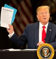 Donald Trump håller upp en New York Times-artikel. Andy Clayton-King / TT NYHETSBYRÅN/ NTB Scanpix