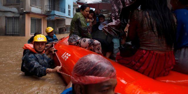 Människor i Katmandu får hjälp att undkomma översvämningarna. NAVESH CHITRAKAR / TT NYHETSBYRÅN