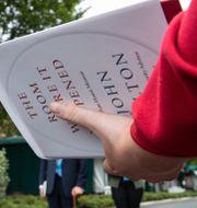 Reporter med boken i handen, Vita husets pressekreterare i bakgrunden.  Alex Brandon / TT NYHETSBYRÅN