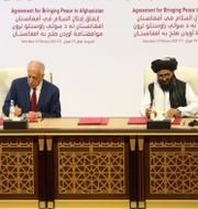 USA:s sändebud Zalmay Khalilzad skriver under fredsavtalet med talibanernas politiske ledare Mullah Abdul Ghani Baradar, 29 februari 2020.   Hussein Sayed / TT NYHETSBYRÅN