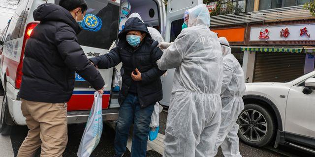 Vårdpersonal hjälper en patient i Wuhan, Kina. TT NYHETSBYRÅN