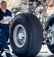 Mekaniker vid däck tillhörande en Airbus A340 vid Frankfurts flygplats i Tyskland.  Michael Probst / TT NYHETSBYRÅN