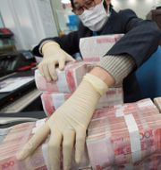 Illustrationsbild: En bankanställd plockar med kinesiska sedlar, januari 2020.  CHINA DAILY / TT NYHETSBYRÅN