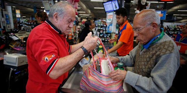Mexikanska män packar sina varor i en tygkasse. GUSTAVO GRAF MALDONADO / TT NYHETSBYRÅN