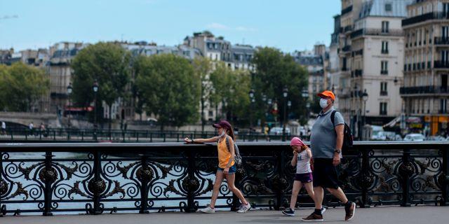 Familj med munskydd i Paris. Kamil Zihnioglu / TT NYHETSBYRÅN