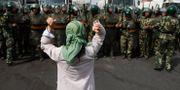 En uigurisk kvinna protesterar mot militärpolisen i Xinjiang.  Ng Han Guan / TT NYHETSBYRÅN/ NTB Scanpix