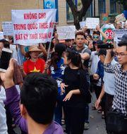 """Demonstranter håller upp ett plakat med texten """"Inget leasande av land till Kina – inte ens för en enda dag"""" i Hanoi. STAFF / TT NYHETSBYRÅN"""
