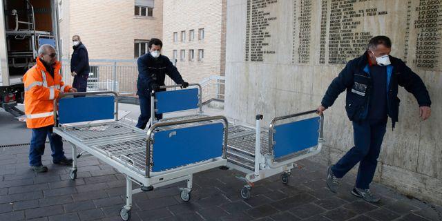 Personal drar in sjukhussängar på ett sjukhus i norra Italien.  Luca Bruno / TT NYHETSBYRÅN