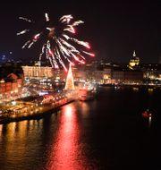 Fyrverkeri över Skeppsbron i Stockholm strax före midnatt på nyårsafton. ANDERS WIKLUND / TT / TT NYHETSBYRÅN