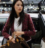 Arkivbild: En kvinna kliver ur en bil på en bilmässa i Peking.  Andy Wong / TT NYHETSBYRÅN/ NTB Scanpix
