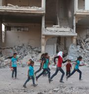 Syriska barn som flytt sina hem i staden Ghouta's al-Marj leker i stad öster om Damaskus. AMER ALMOHIBANY / AFP