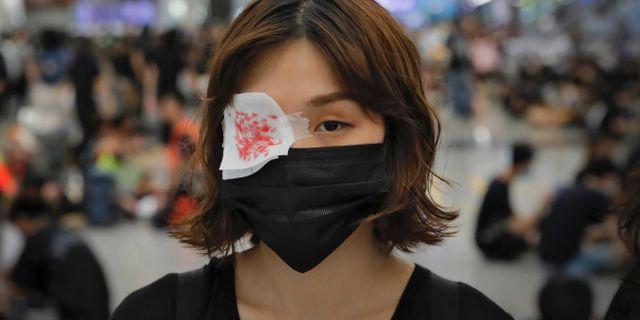 En demonstrant har på sig en ögonlapp. Kin Cheung / TT NYHETSBYRÅN