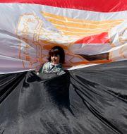 En ung flicka står invirad i en egyptisk flagga när palestinier samlas i Gaza city efter beskedet att Hamas och Fatah är överens om försoning mellan styrena på Gaza och Västbanken. MAHMUD HAMS / AFP