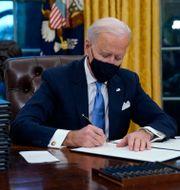 Biden skrev under flera presidentorder redan första dagen i Vita huset.  Evan Vucci / TT NYHETSBYRÅN