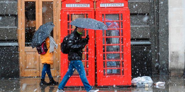 Invånare i London skyddar sig mot snön med paraplyer.  DANIEL SORABJI / AFP