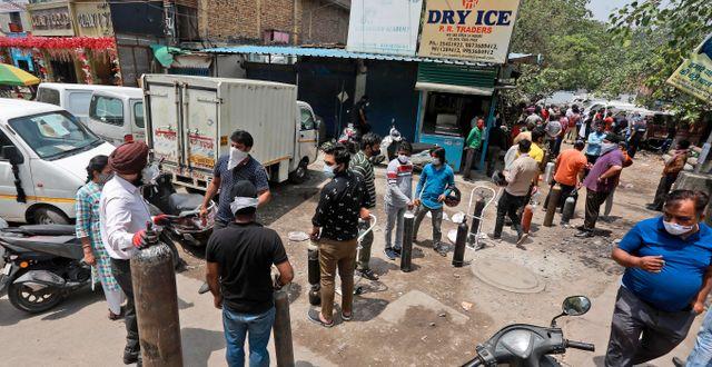 Folk står i kö för att fylla på syrgas i New Delhi.  TT NYHETSBYRÅN