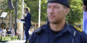 Ulf Kristersson och en polis. Anders Wiklund/TT / TT NYHETSBYRÅN