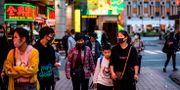 Kineser skyddar sig med ansiktsmasker. ANTHONY WALLACE / AFP