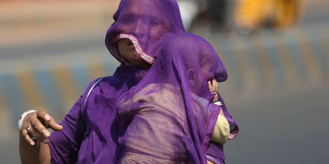 En kvinna försöker skydda sig och sitt barn från värmen, arkivbild. Mahesh Kumar A. / TT NYHETSBYRÅN