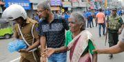 En äldre kvinna får hjälp bort från en av explosionsplatserna.  Eranga Jayawardena / TT NYHETSBYRÅN