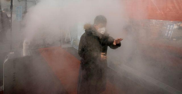 Kinesisk invånare besprutas med desinfektionsspray. TT NYHETSBYRÅN
