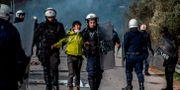 Grekisk polis på Lesbos griper en migrant. ANGELOS TZORTZINIS / TT NYHETSBYRÅN