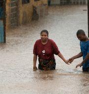 En man hjälper en kvinna i Pemba i Moçambique. MIKE HUTCHINGS / TT NYHETSBYRÅN