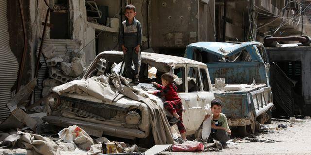 Syriska pojkar leker på en förstörd bil i Douma utanför Damaskus. Bilden är tagen den 19 april.  STRINGER / AFP