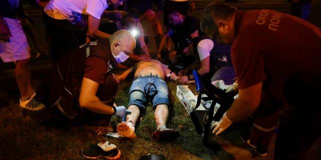 Sjukvårdare behandlar en skadad demonstrant i Minsk. Sergei Grits / TT NYHETSBYRÅN