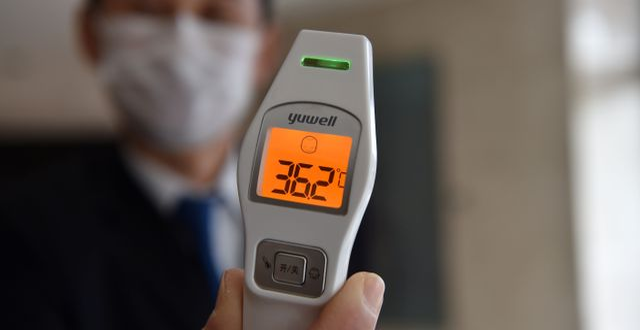 En hotellanställd visar en termometer vid entrén där gäster screenas. HECTOR RETAMAL / AFP