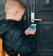 """Pojke öppnar dörr med """"smart locks"""". Pressfoto: Assa Abloy"""