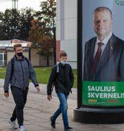 Boende i Vilnius går förbi valaffisch av premiärministern. Mindaugas Kulbis / TT NYHETSBYRÅN