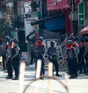 Arkivbild: Beväpnade poliser står vakt på en huvudgata i Myanmars största stad Rangoon, 5 mars.  STR / TT NYHETSBYRÅN