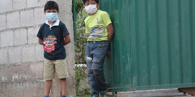 Pojkar i Zambiza utanför Ecuadors huvudstad Quito väntar på att militären ska dela ut mat under coronapandemin. Dolores Ochoa / TT NYHETSBYRÅN