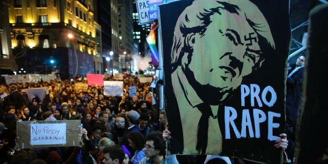 En man håller upp ett plakat där Donald Trump anklagas för att vara en våldtäktsman. KENA BETANCUR / AFP