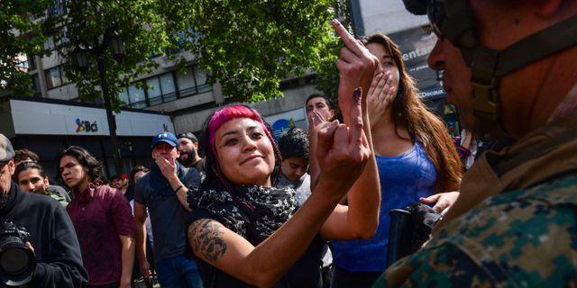 En demonstrant ger en militär fingret i Santiaho. MARTIN BERNETTI / AFP