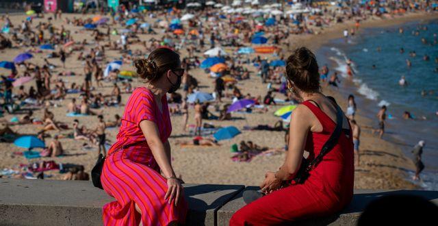 Två kvinnor kollar ut över en fullsatt strand i Barcelona den 18 juli. Emilio Morenatti / TT NYHETSBYRÅN