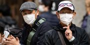 Åskådare med ansiktsmasker tittar på Tokyo Marathon. PHILIP FONG / TT NYHETSBYRÅN
