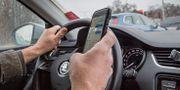 Person kör bil och håller i mobiltelefon samtidigt. Martina Holmberg / TT / TT NYHETSBYRÅN