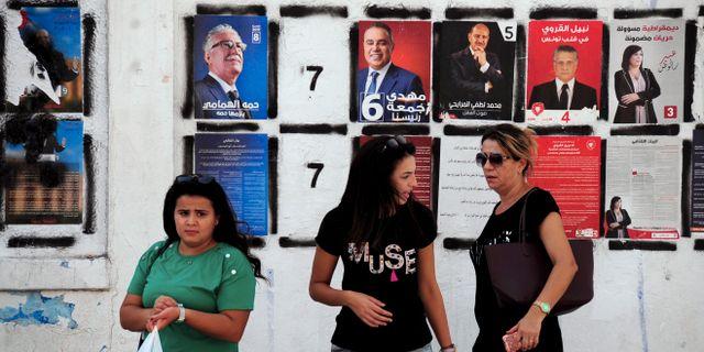 Tre kvinnor passerar affischer med presidentkandidaterna dagen före presidentvalet. Hassene Dridi / TT NYHETSBYRÅN