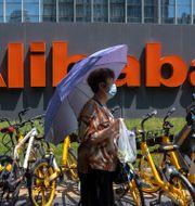 Illustrationsbild. Kvinna går förbi Alibaba-skylt. Mark Schiefelbein / TT NYHETSBYRÅN