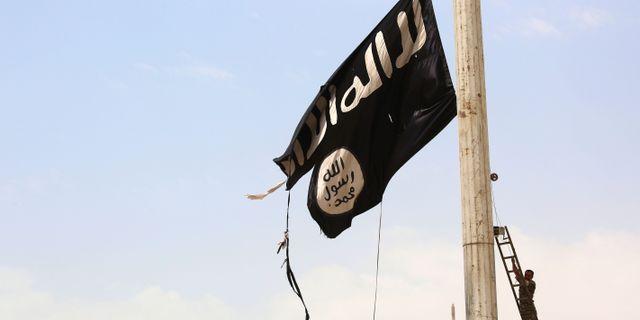 Illustrationsbild. En medlem ur de kurdiska styrkorna tar ner en IS-flaga i staden Tabqa.  DELIL SOULEIMAN / AFP