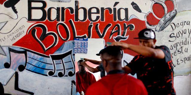 En man klipper håret i Caracas i mars. Natacha Pisarenko / TT NYHETSBYRÅN