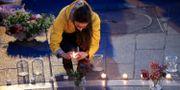 En kvinna tänder ett ljus vid Place Saint-Michel.  GONZALO FUENTES / TT NYHETSBYRÅN