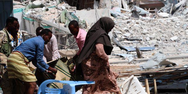 En kvinna går förbi den plats där al-Shabaqab genomförde ett attentat i torsdags.  ABDIRAZAK HUSSEIN FARAH / AFP