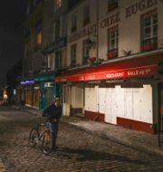 En ensam man leder sin cykel utanför en stängd restaurang i Montmartre, Paris.  Michel Euler / TT NYHETSBYRÅN
