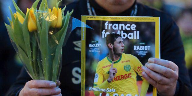 Fotbollsfans håller i tidning med Emiliano Sala på omslaget. David Vincent / TT NYHETSBYRÅN/ NTB Scanpix