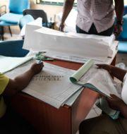 Valarbetare skriver ner resultaten från vallokaler i staden Port Harcourt.  YASUYOSHI CHIBA / AFP